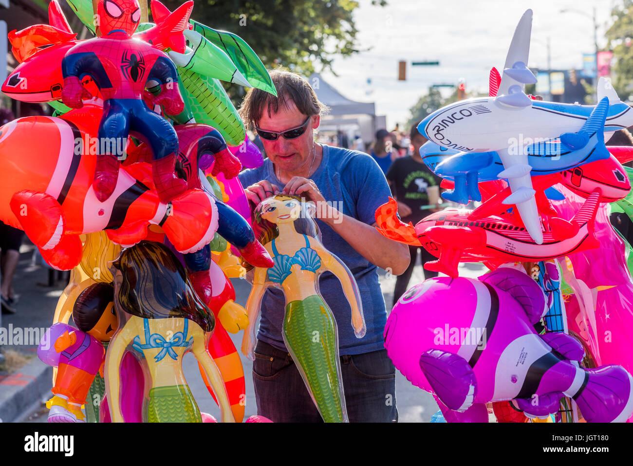 Inflatable toy vendor, Khatsalano Festival, Kitsilano, Vancouver, British Columbia, Canada. Stock Photo