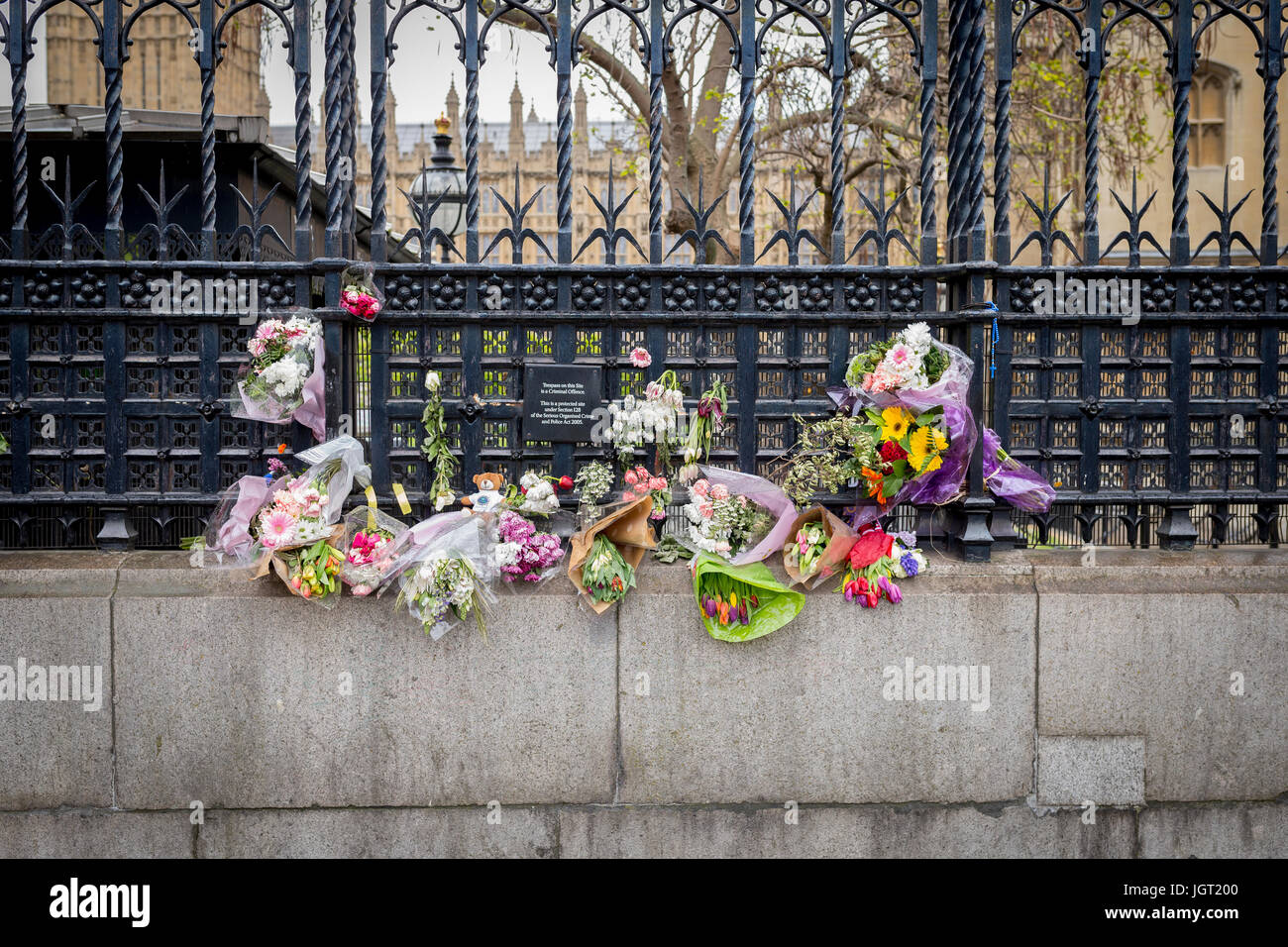 Flowers and floral tributes left outside the Carriage Gate of The Houses of Parliament in memory of the 22 March - Stock Image