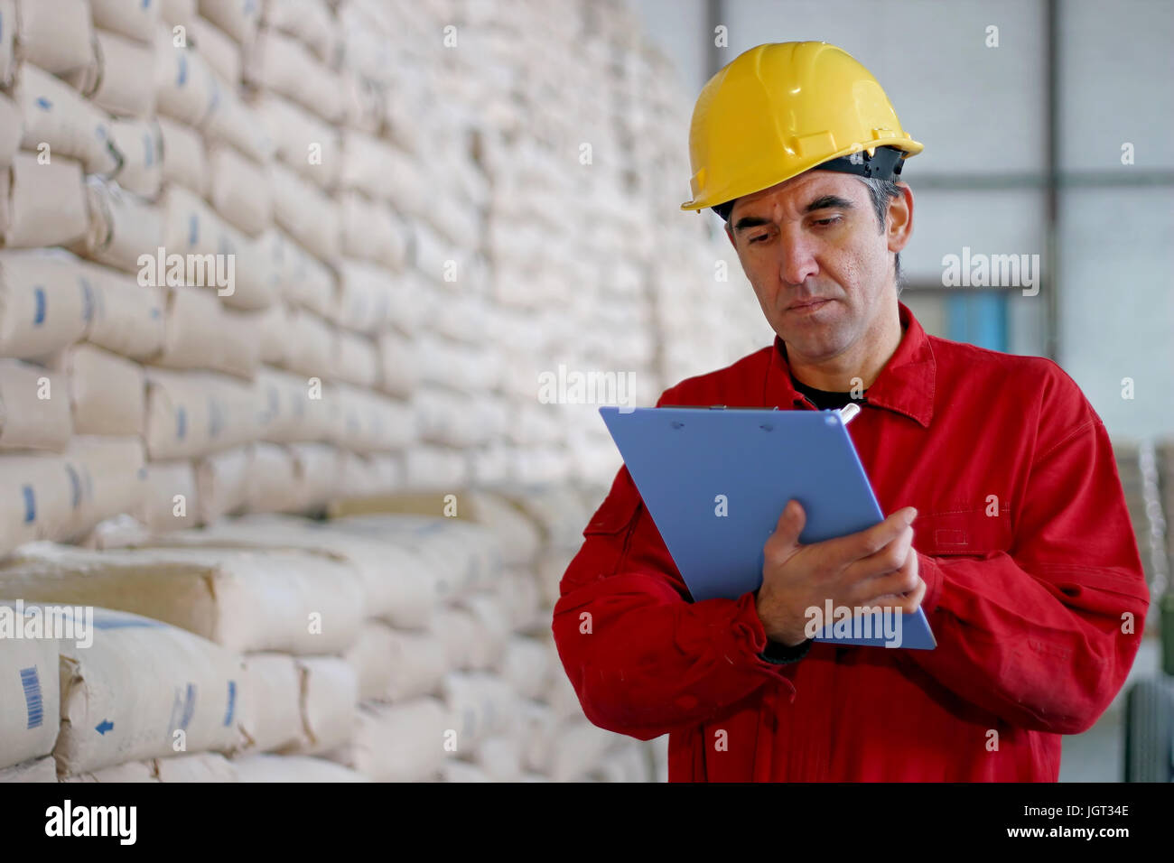 Worker in distribution warehouse beside big pile of sacks at large warehouse in modern factory. - Stock Image