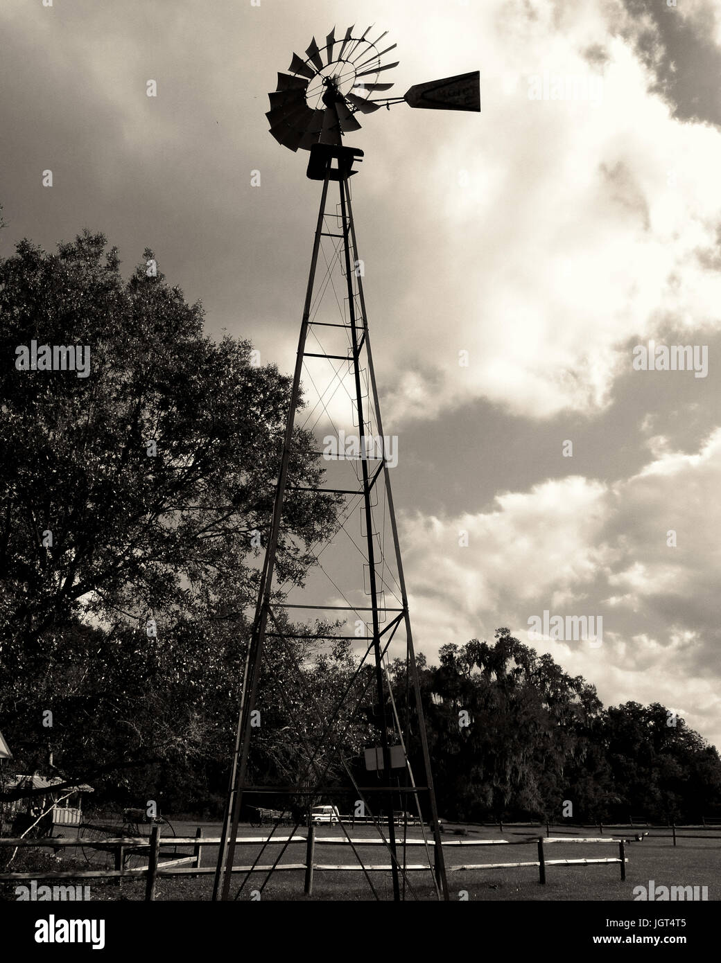 Windmill on a cloudy day while sun is setting - Stock Image