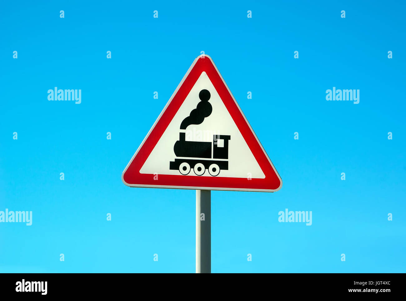 Railroad Level Crossing Sign without barrier or gate ahead the road, beware of train roadside steam engine locomotive - Stock Image