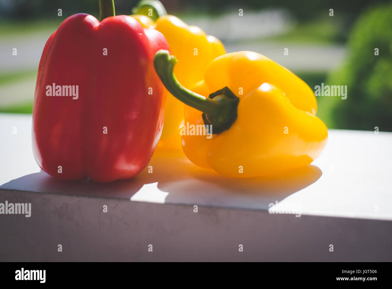 Three peppers, yellow and red, displayed on a counter. - Stock Image