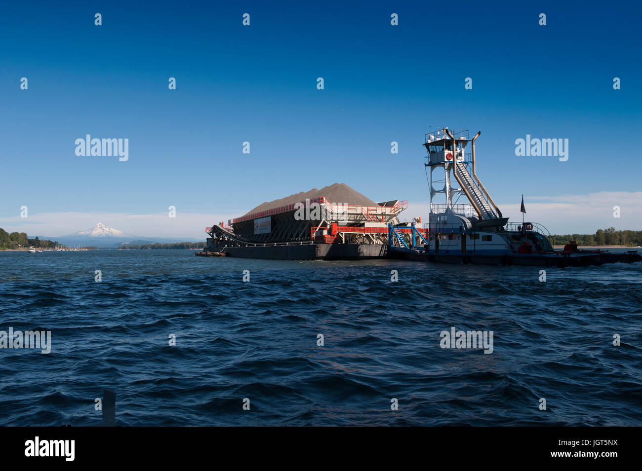 A towboat pushes an aggregate loaded barge up the Columbia River with snow capped Mt. Hood in the distance - Stock Image