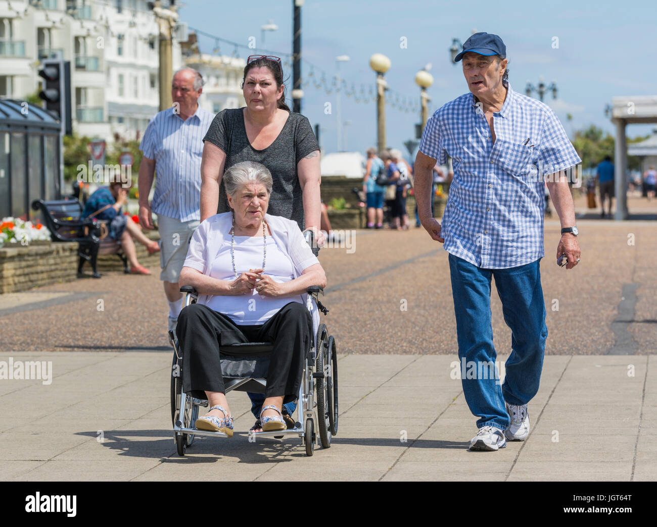Elderly disabled woman being pushed in a wheelchair. - Stock Image