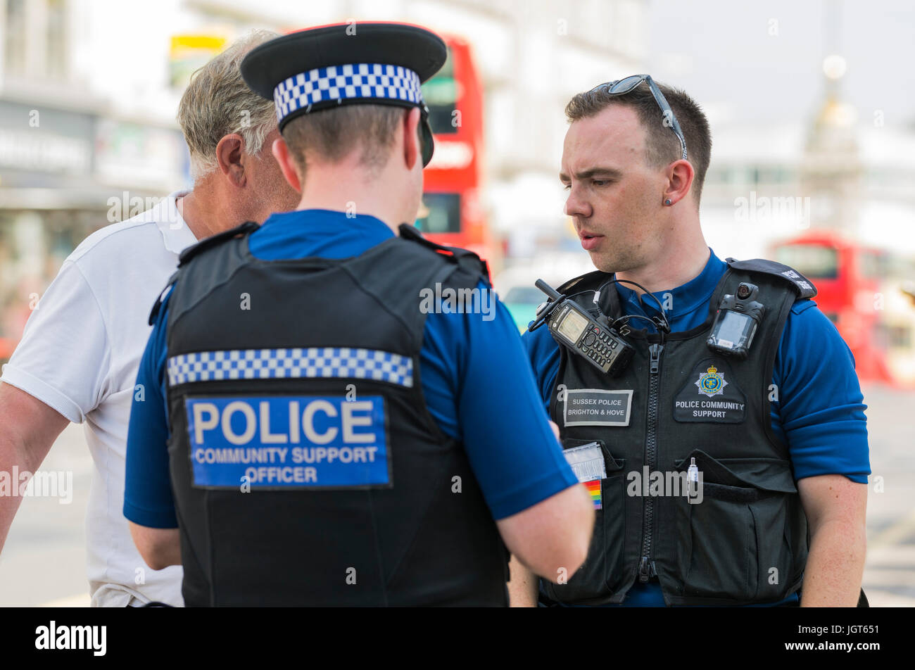 PCSOs (Police Community Support Officers) speaking to someone on the streets of Brighton, East Sussex, England, - Stock Image