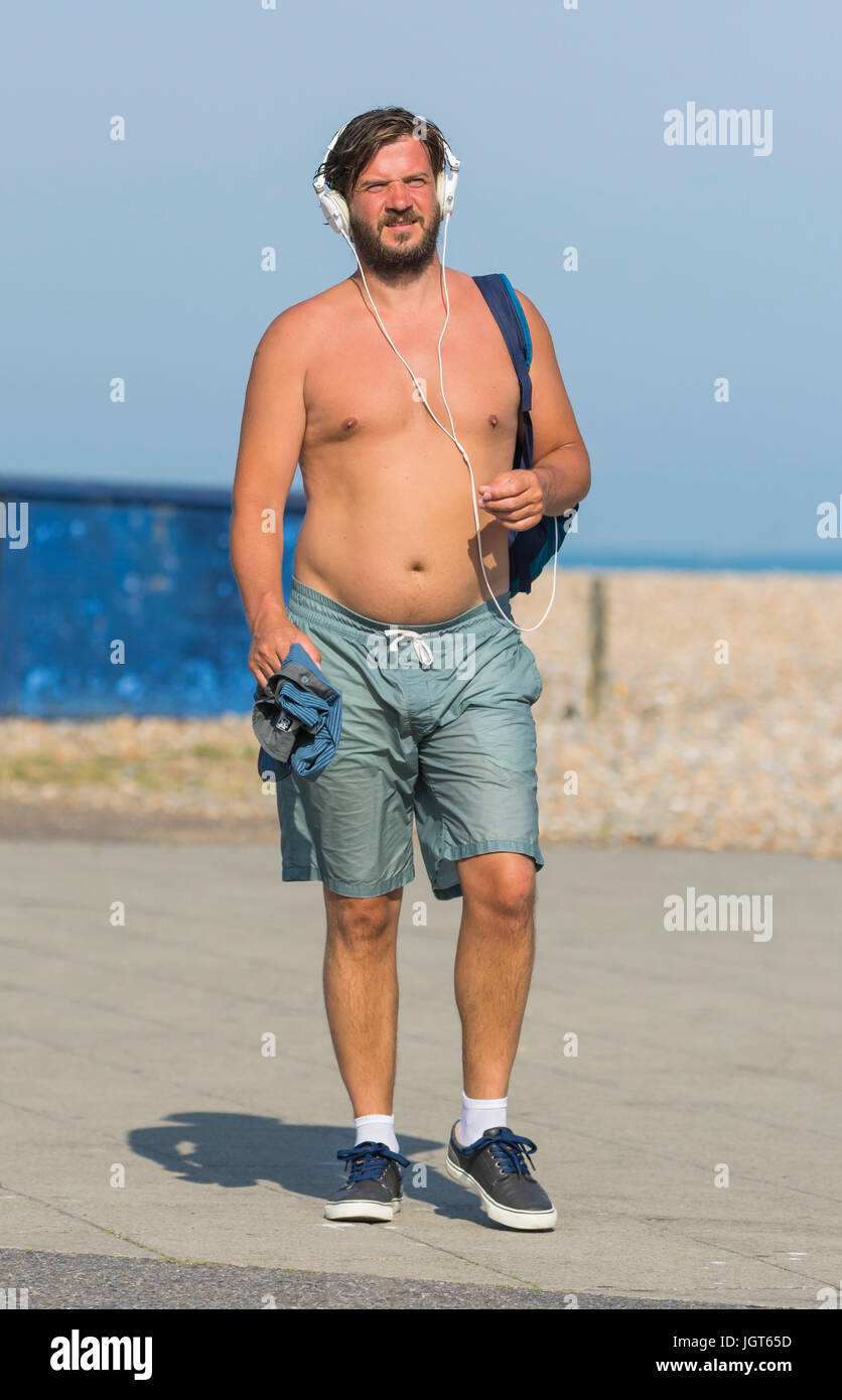 Shirtless man wearing shorts and headphones on a hot day in Summer, walking along listening to music. - Stock Image