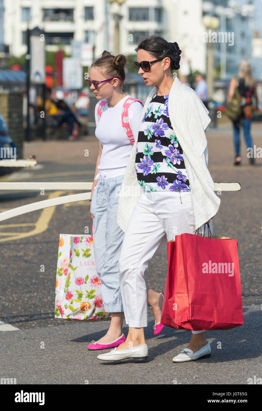 Mother and Daughter out together on a shopping spree, carrying shopping bags. - Stock Image