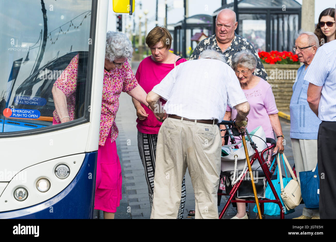 Elderly man helping an elderly woman getting off a bus. Helping the aged. Assisting concept. Giving assistance concept. - Stock Image