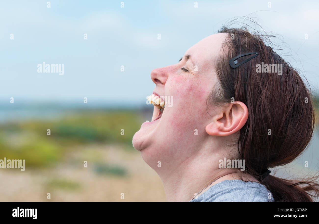 Happy young woman with mouth wide open laughing hysterically until it hurts. - Stock Image