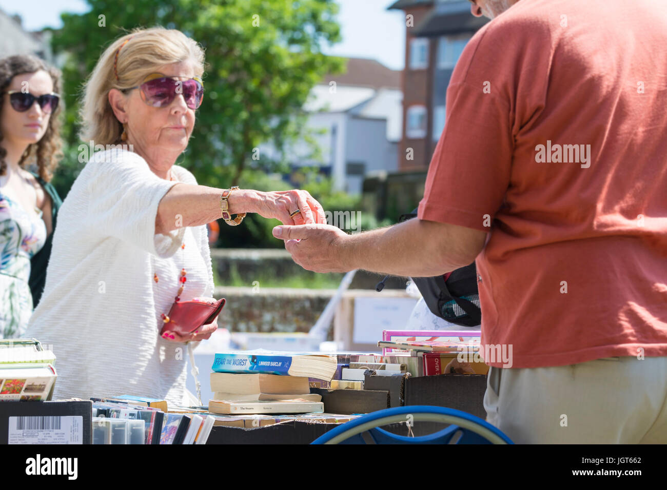 Woman paying for goods at an outdoor market stall with cash, - Stock Image
