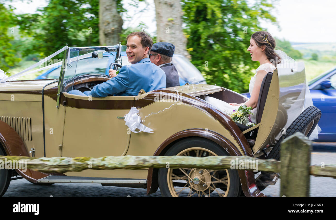 Bride and Groom travelling in an old car on their wedding day. Happy couple. Getting married in the UK. Newly weds. - Stock Image