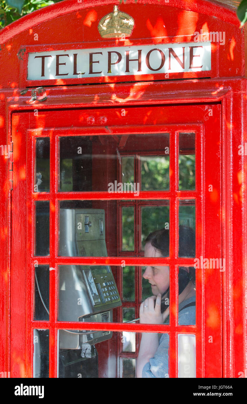 K6 telephone box. Woman using the phone in an old BT K6 telephone box that has recently been painted, in the UK. - Stock Image