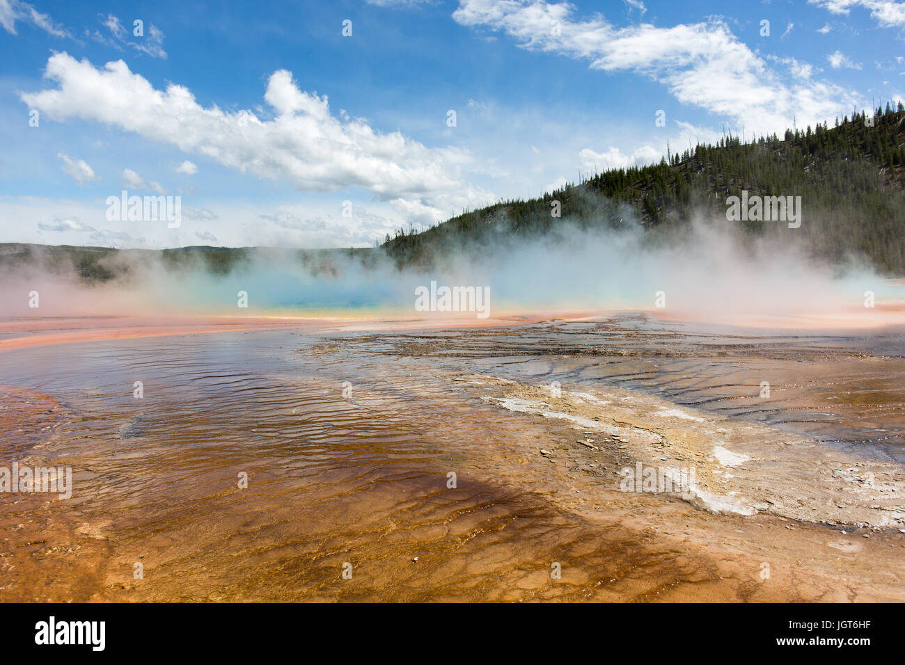 Grand Prismatic Spring covered in steam on a cold windy but sunny day. Midway Geyser Basin, Yellowstone National - Stock Image