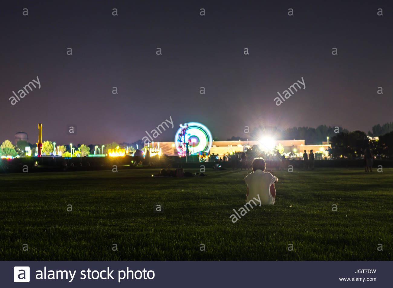 a young boy watching the fair, waiting for a fireworks show at the close of the Ankeny Summerfest, an annual summer - Stock Image