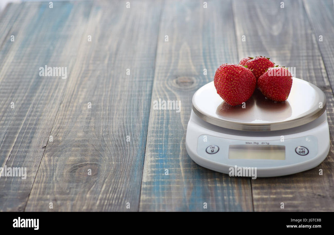 Three ripe strawberry berries lie on electronic kitchen scales - Stock Image