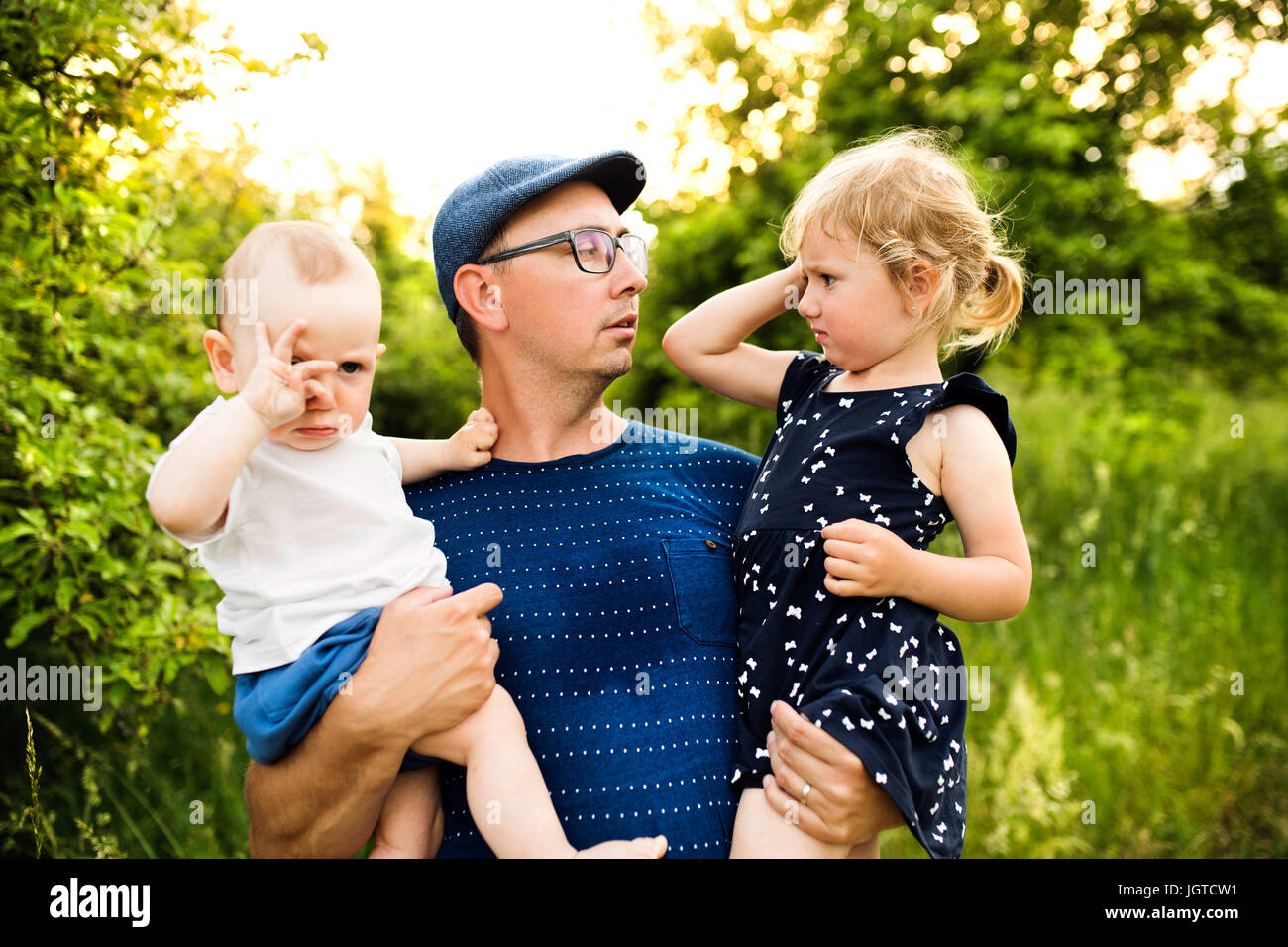 Young father with little children in sunny summer nature Stock Photo