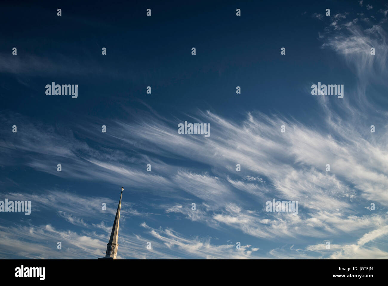 Church steeple with wispy cloud formations as a background. - Stock Image