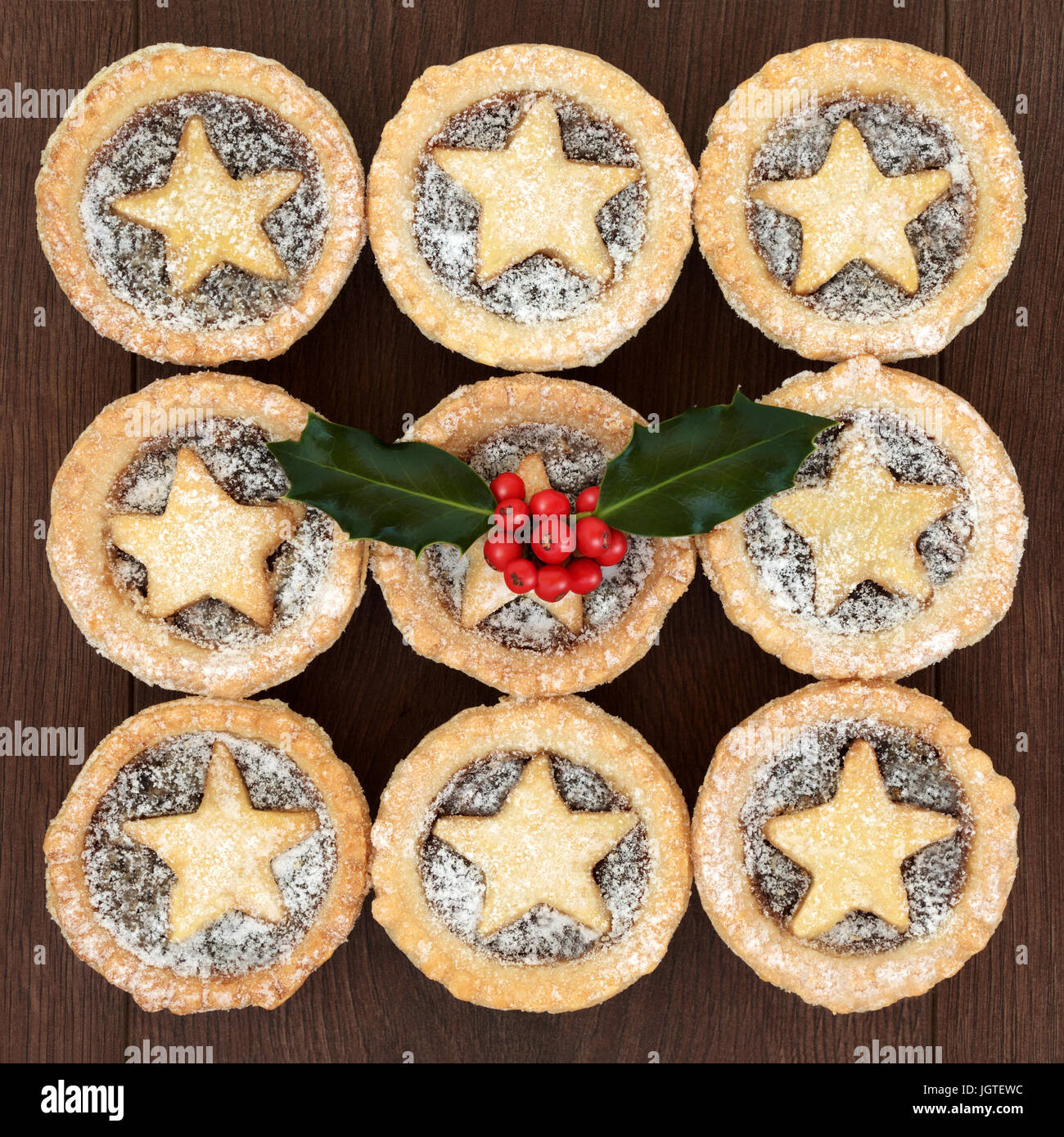 Homemade christmas mince pies with pastry stars and icing sugar dusting, holly and red berries on oak wood background. Stock Photo