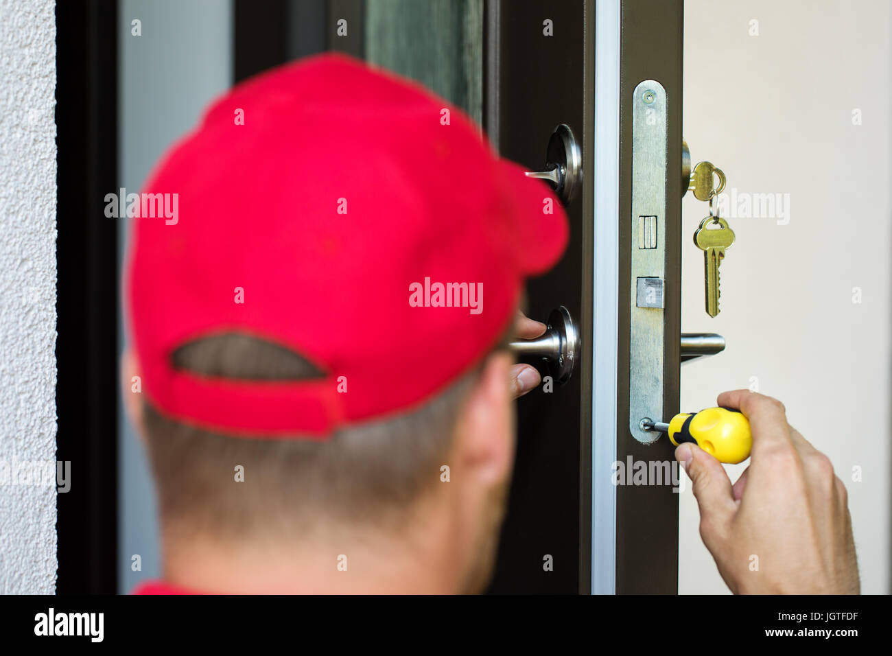 door lock service - locksmith working with screwdriver - Stock Image
