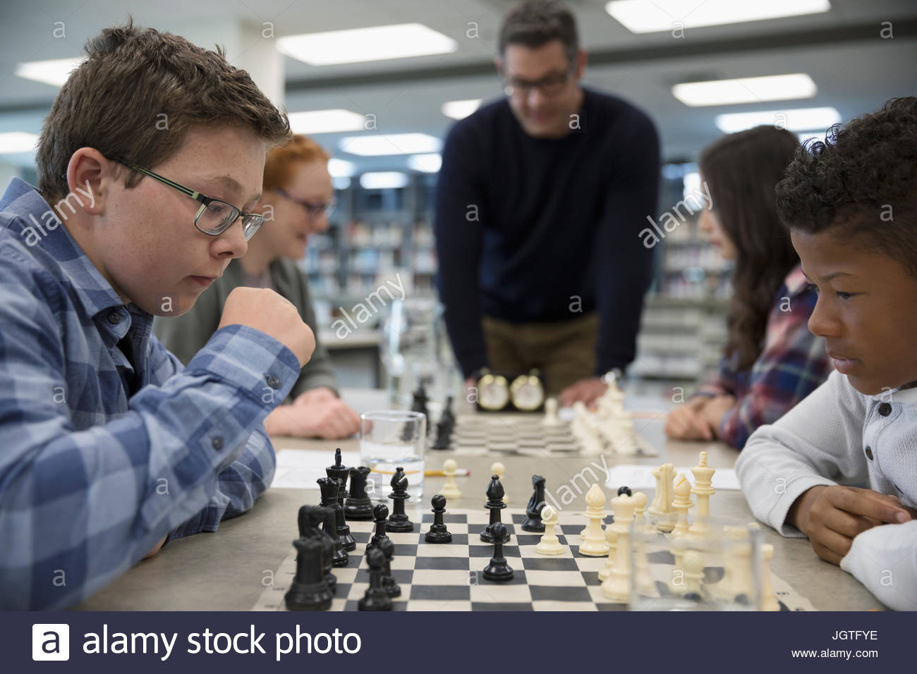 Focused boy middle school students playing chess in chess club - Stock Image