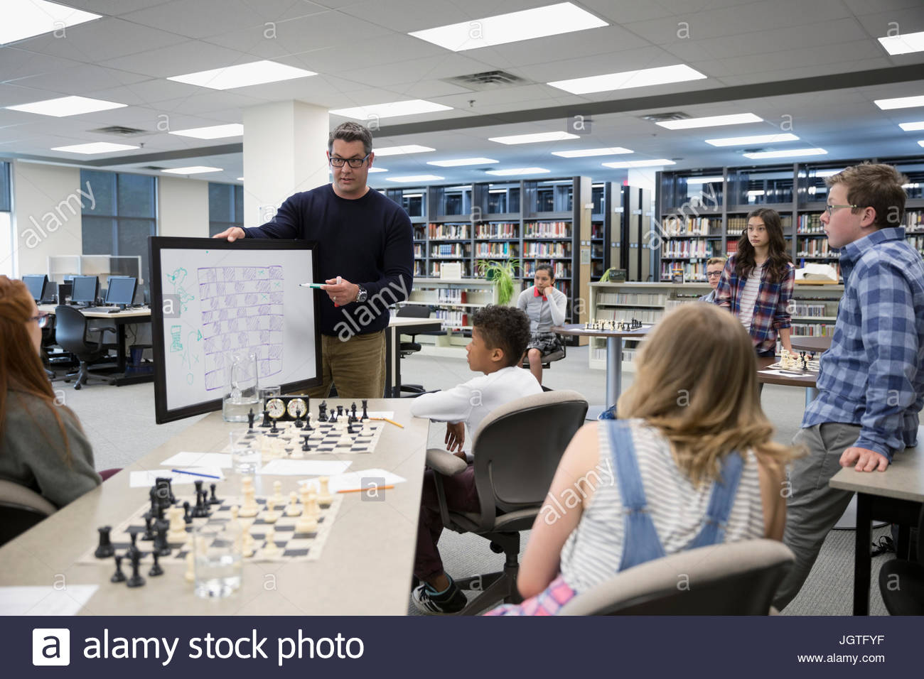 Teacher with whiteboard leading chess club lesson in library - Stock Image