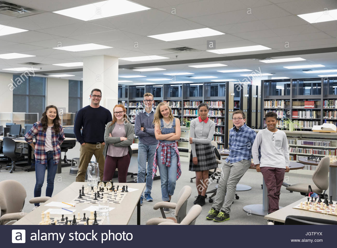 Portrait confident teacher and middle school student chess club in library - Stock Image