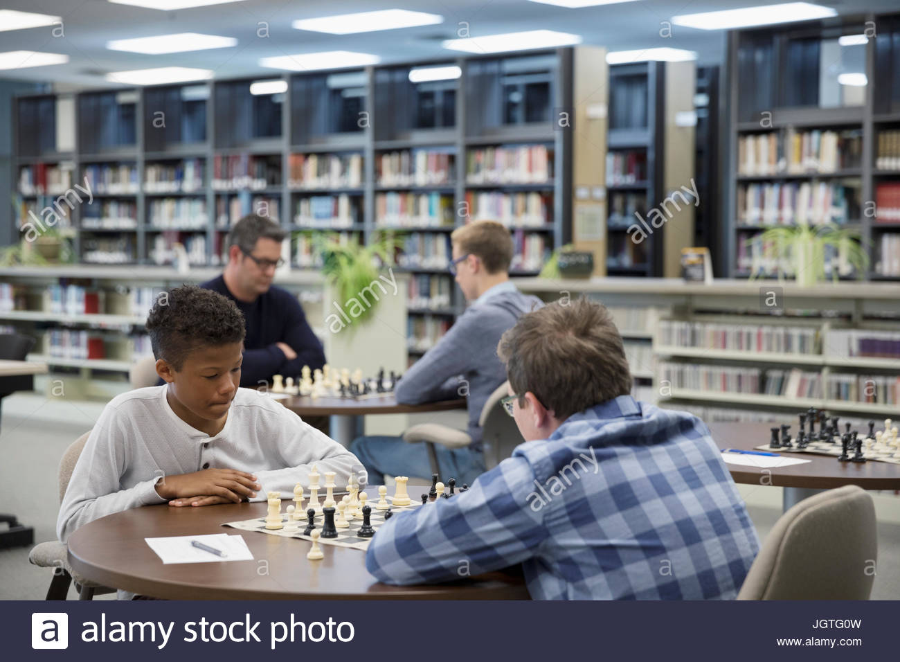 Middle school boy students playing chess in chess club - Stock Image