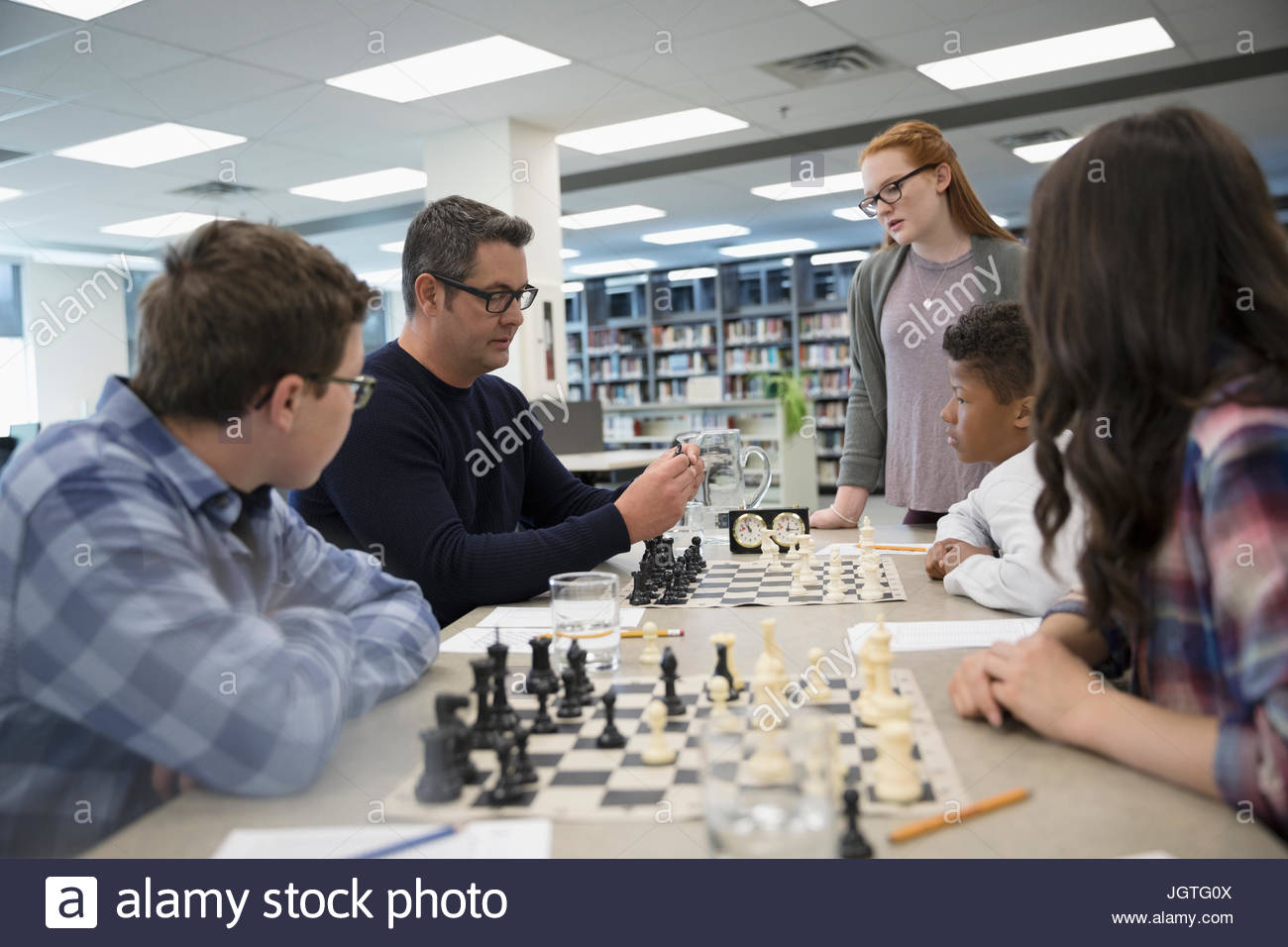 Teacher leading chess club meeting in library - Stock Image