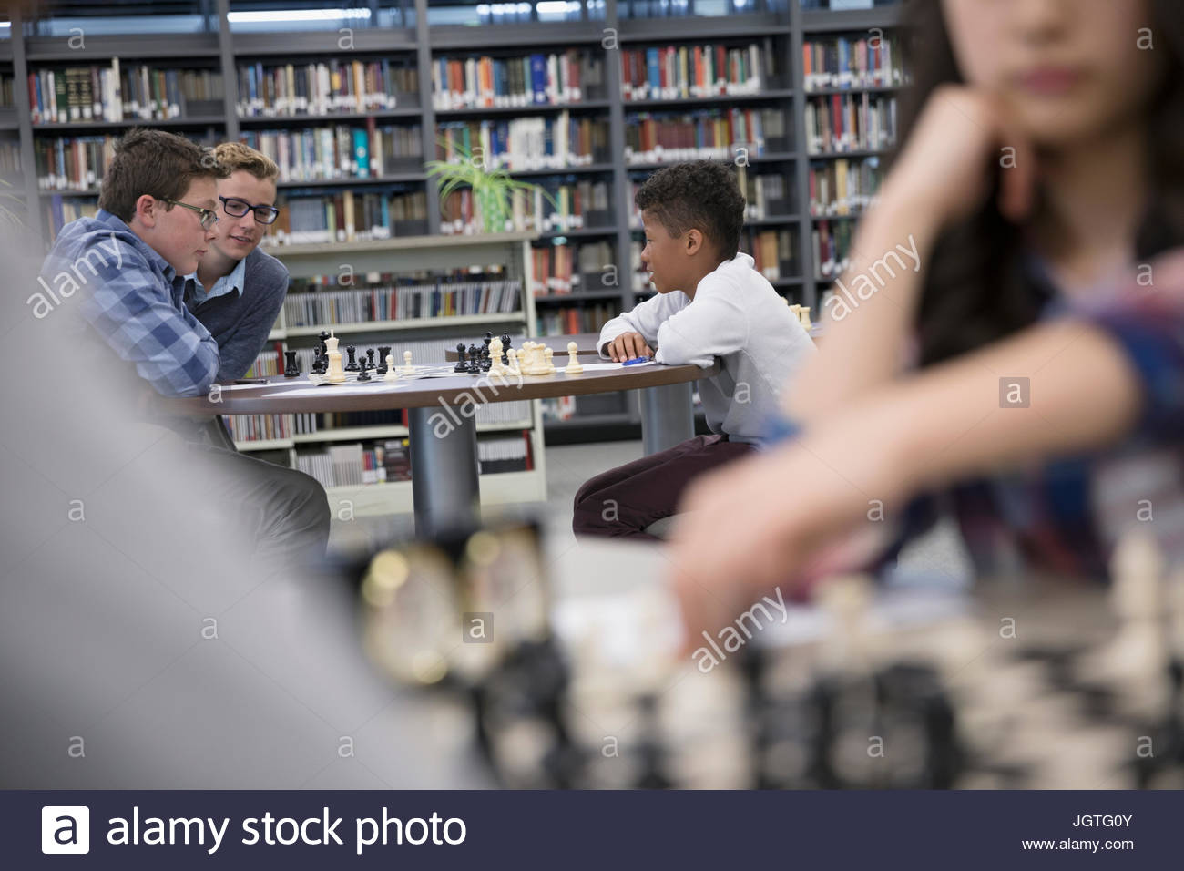 Middle school boy students playing chess in chess club library - Stock Image