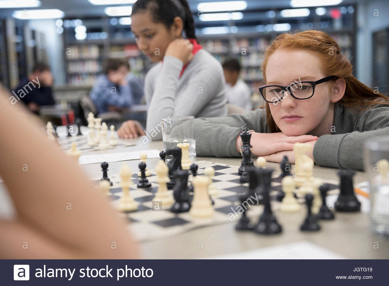 Focused girl middle school student playing chess in chess club library - Stock Image