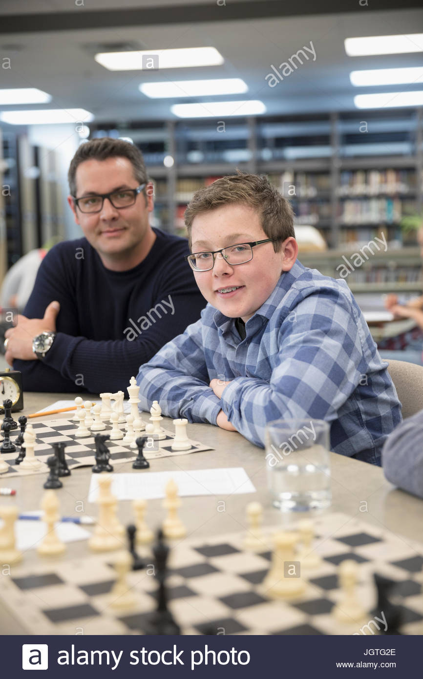 Portrait confident teacher and boy middle school student playing chess in chess club library - Stock Image