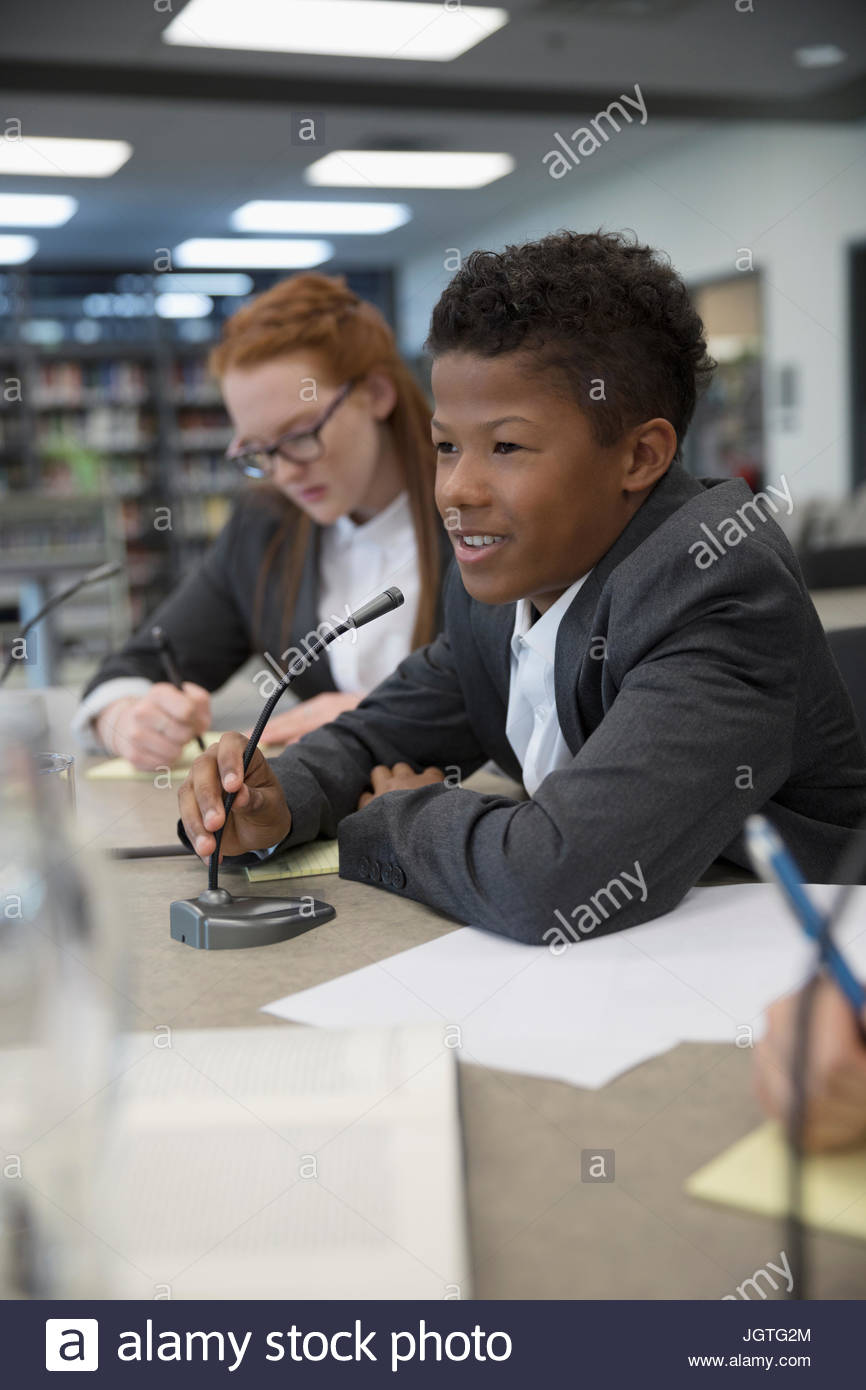 Smiling boy middle school student talking into microphone in debate club - Stock Image