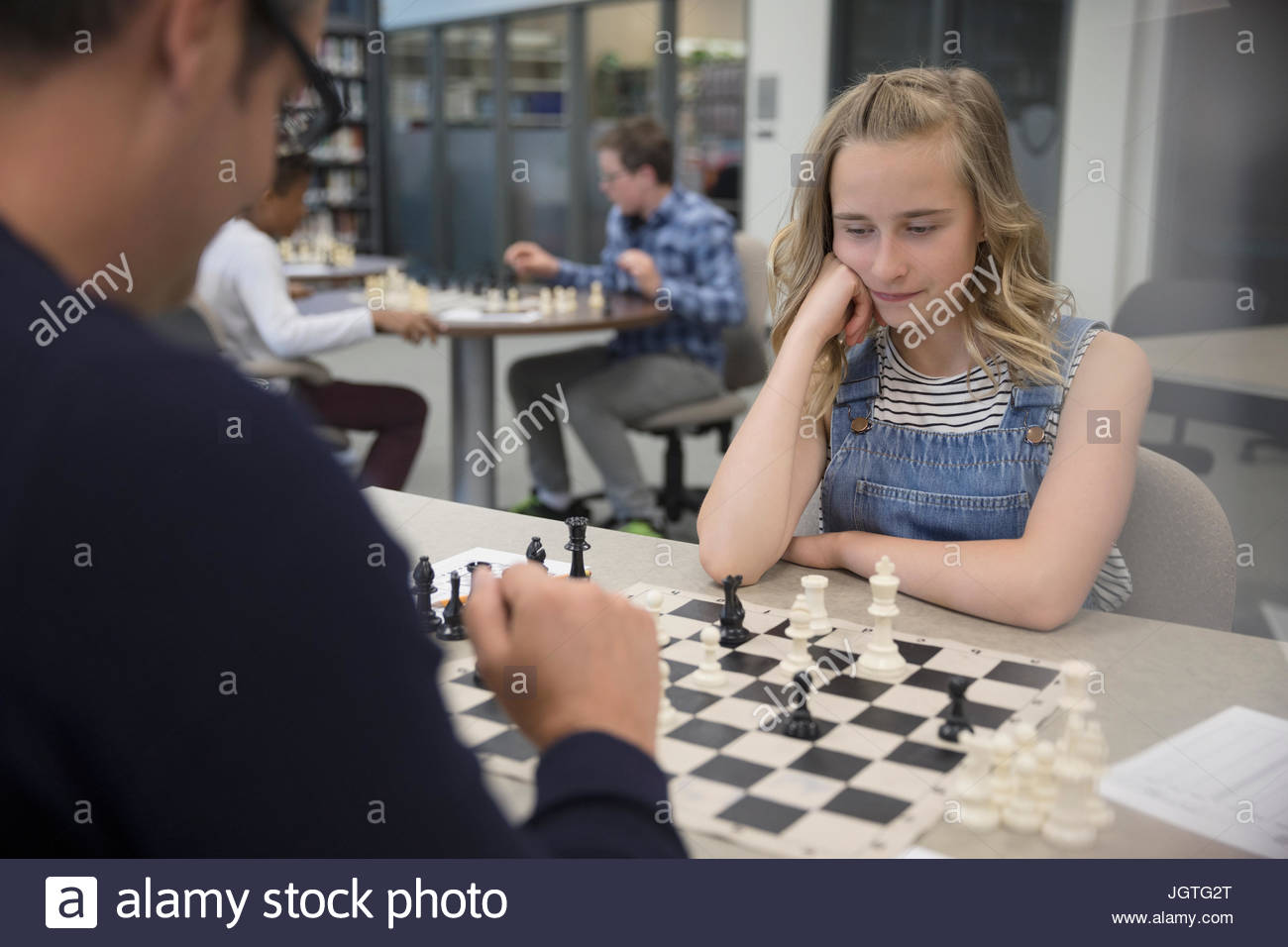 Teacher and girl middle school student playing chess in chess club - Stock Image