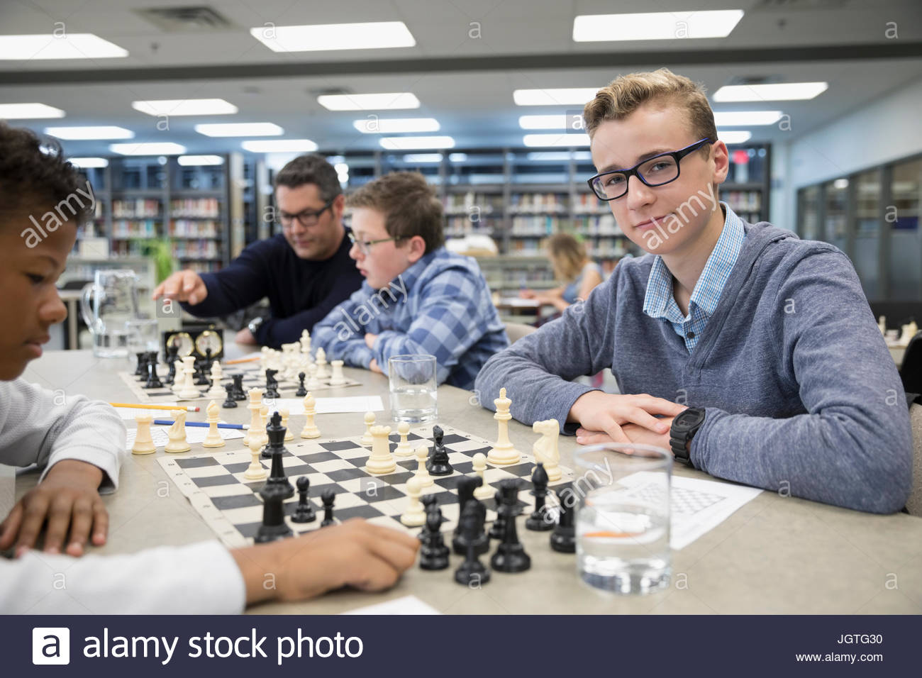 Portrait confident boy middle school student playing chess in chess club library - Stock Image
