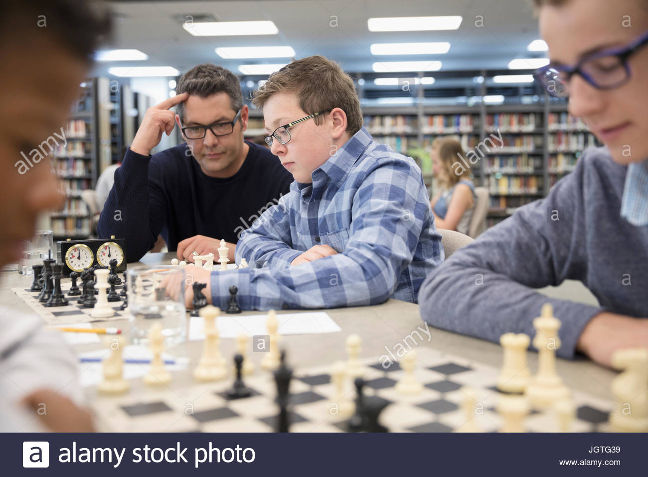 Teacher helping boy middle school student playing chess in chess club library - Stock Image