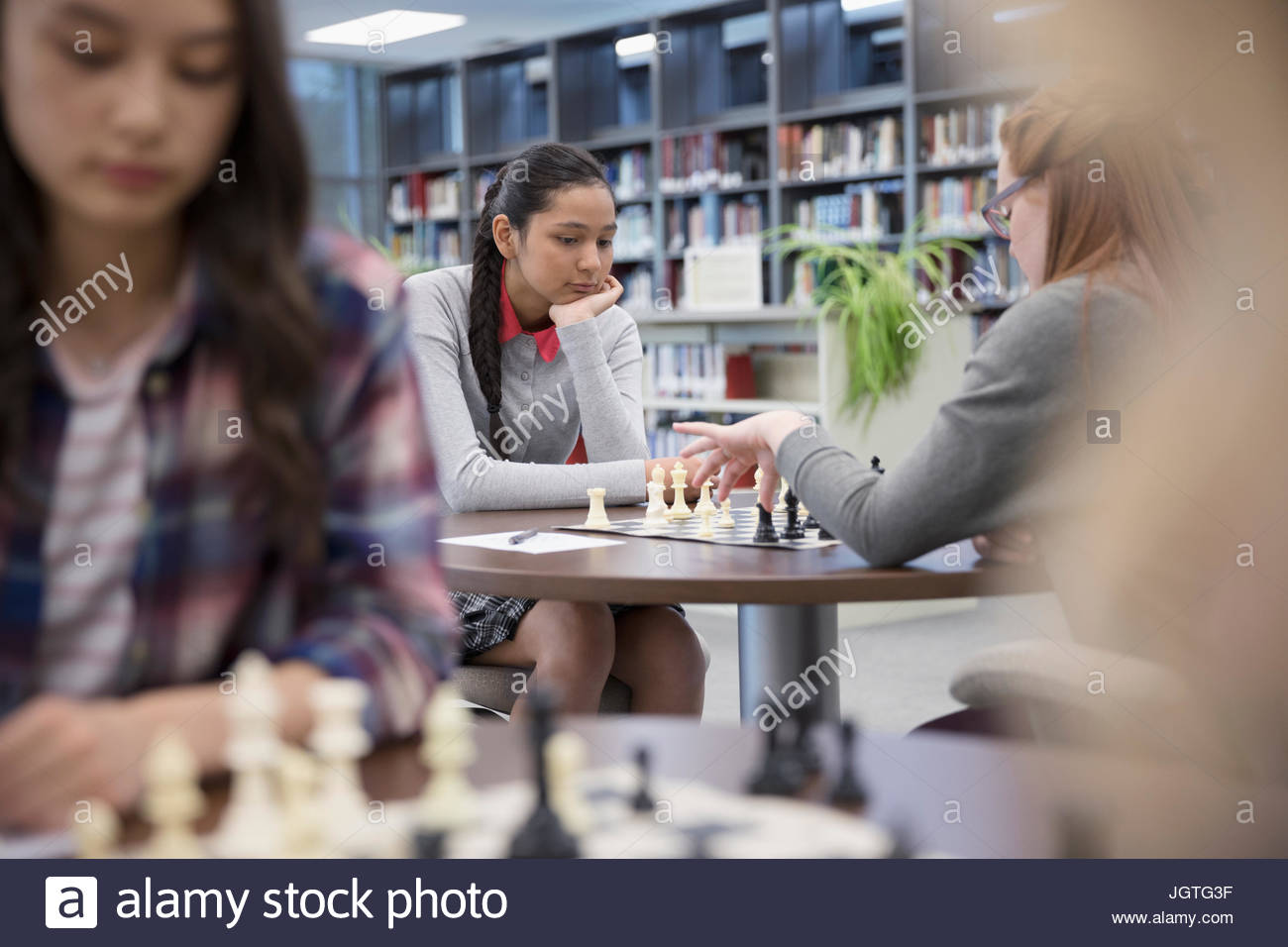 Focused middle school girl student playing chess in chess club library - Stock Image