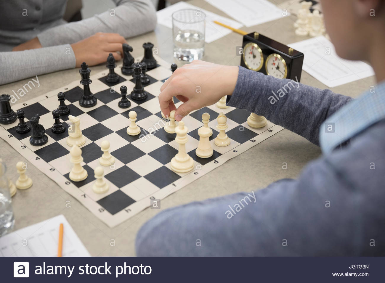 Close up middle school students playing chess in chess club - Stock Image