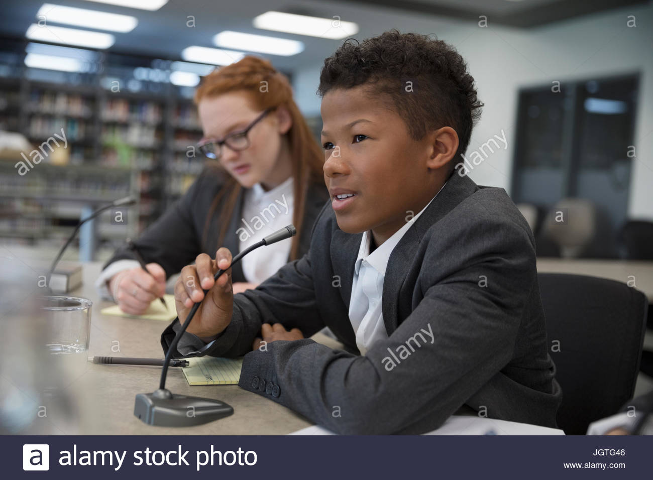 Boy middle school student talking into microphone in debate club - Stock Image