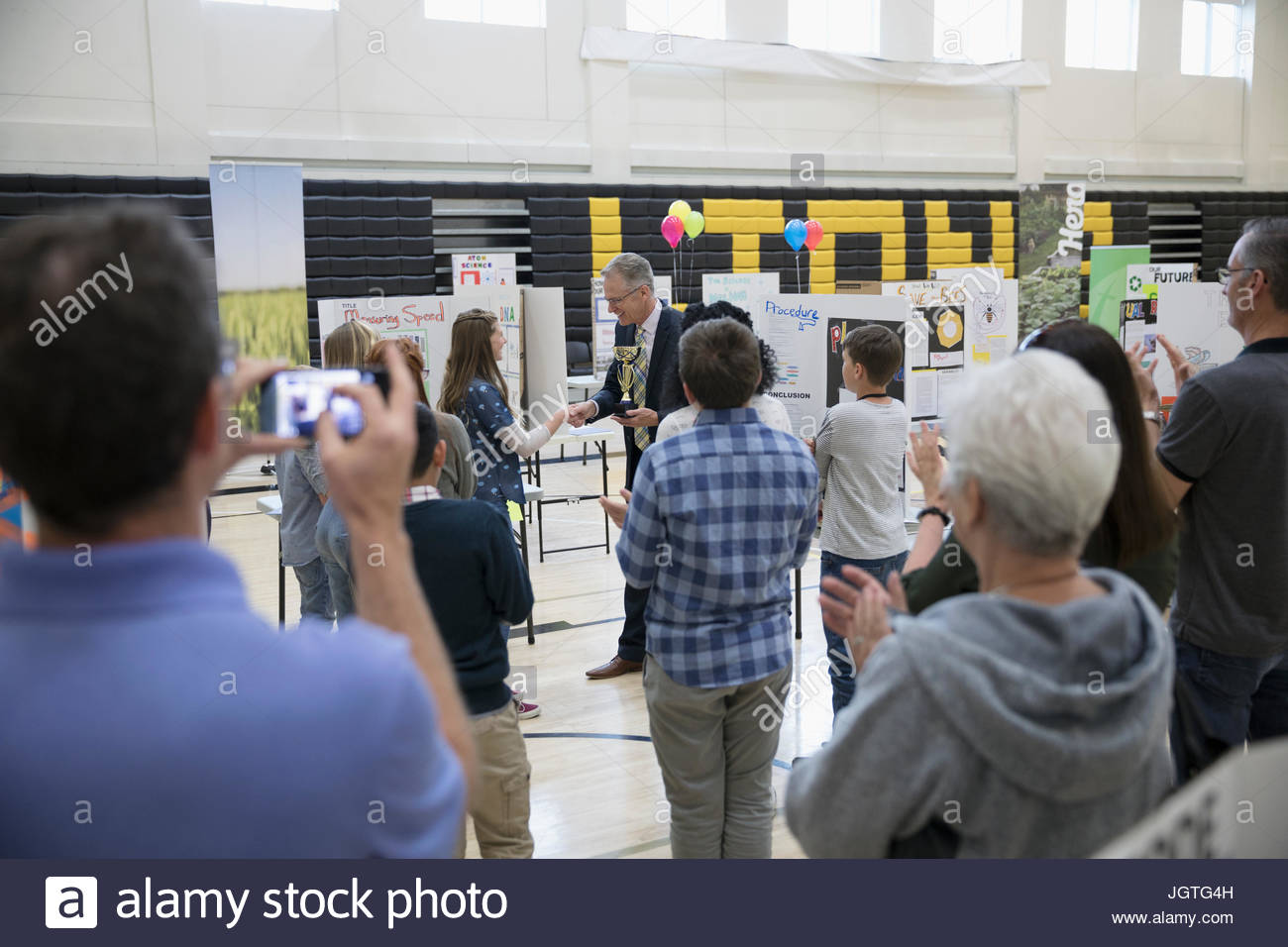 Science teacher awarding middle school student at science fair - Stock Image