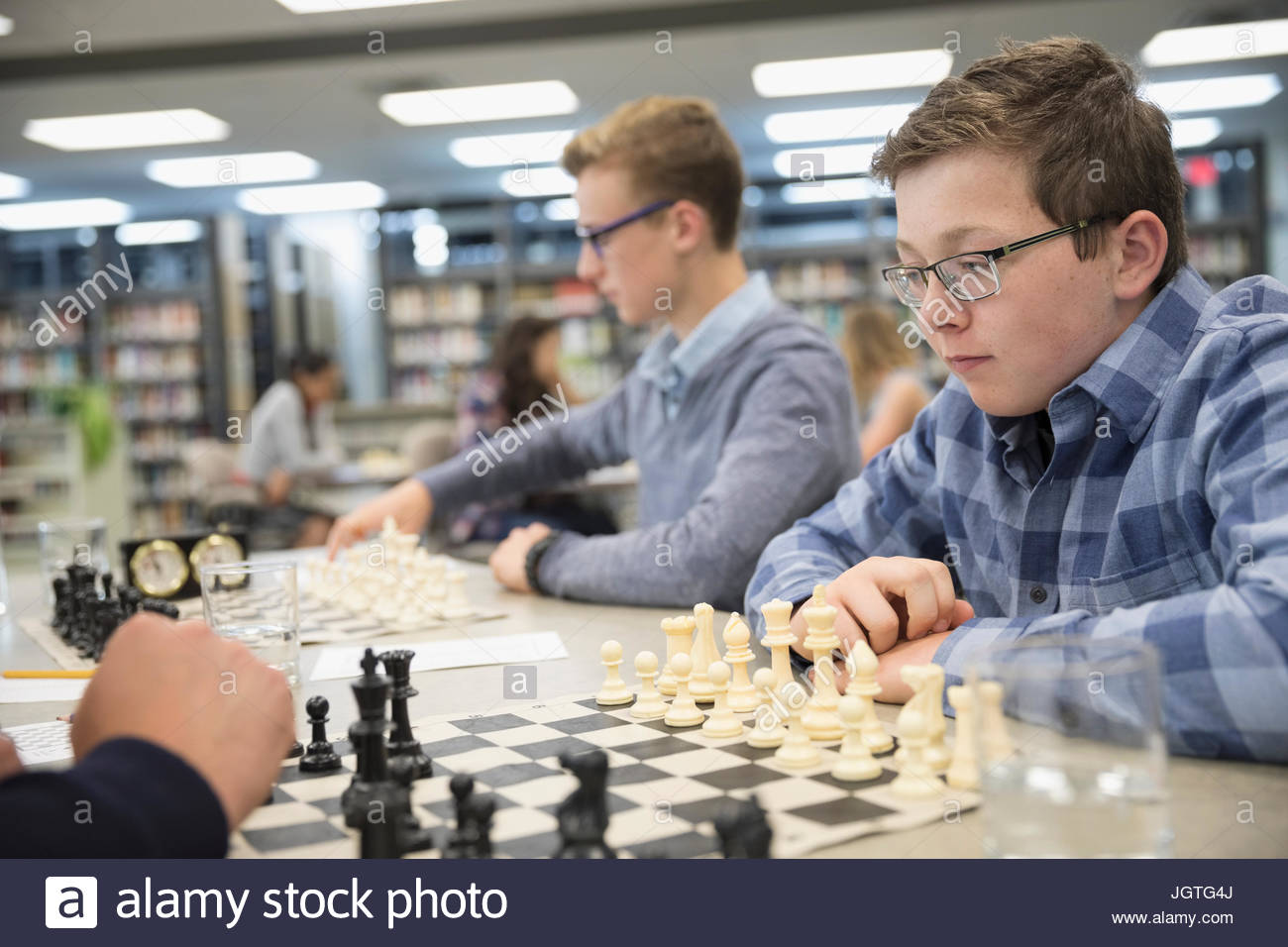 Focused male middle school student playing chess in chess club - Stock Image
