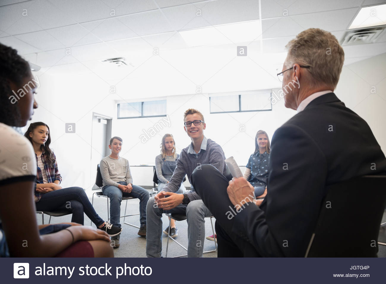 Teacher and middle school students talking in debate classroom - Stock Image