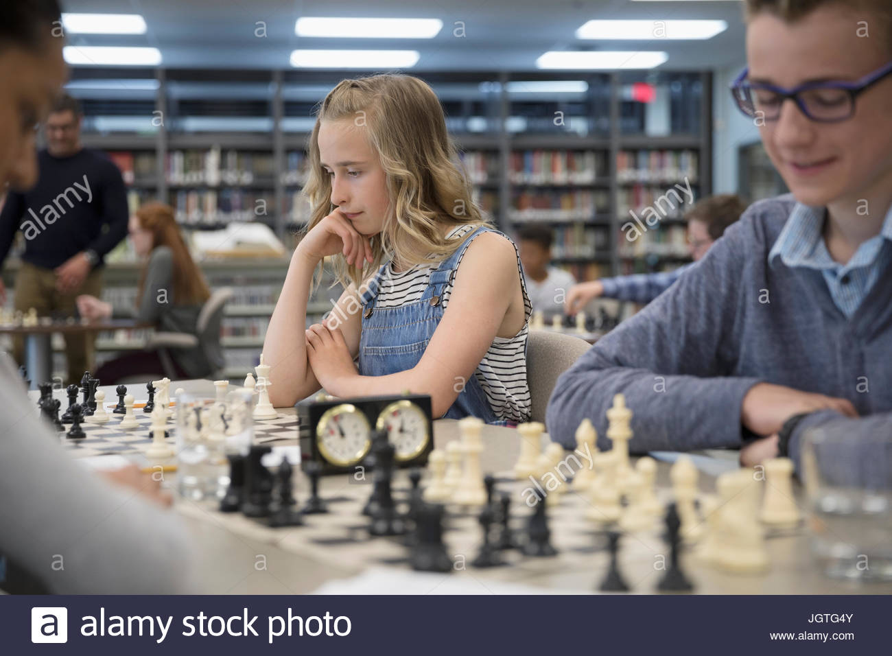 Middle school students playing chess in chess club - Stock Image