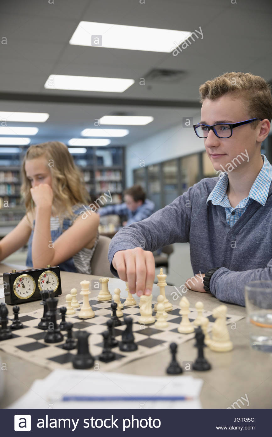 Boy middle school student playing chess in chess club - Stock Image