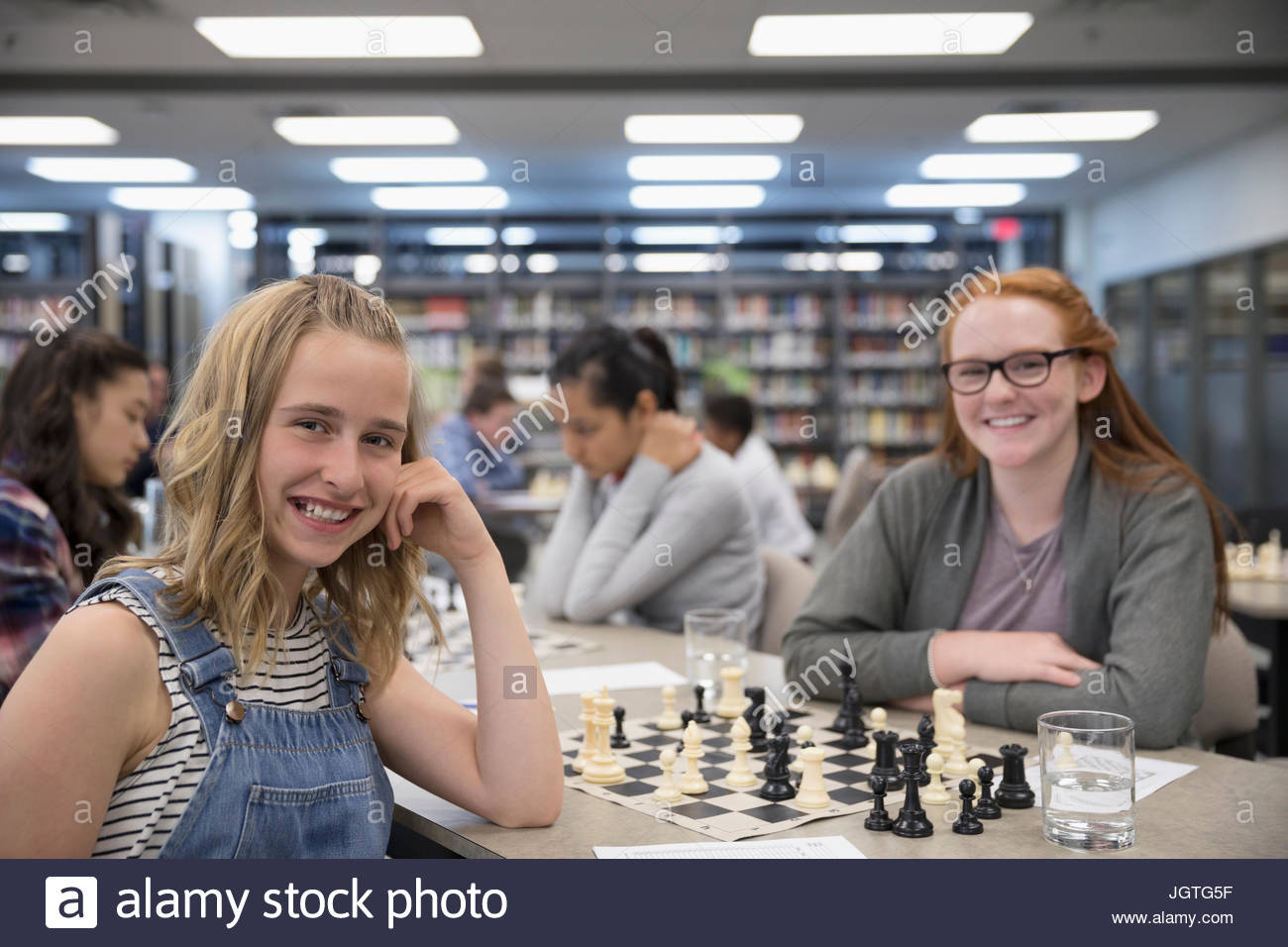 Portrait smiling girl middle school students playing chess in chess club library - Stock Image