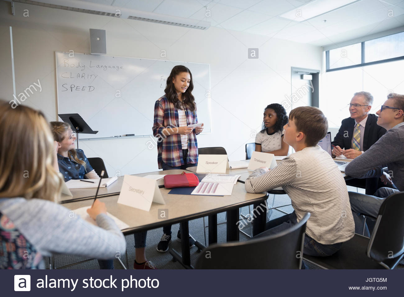 Girl middle school student speaking in debate club classroom - Stock Image