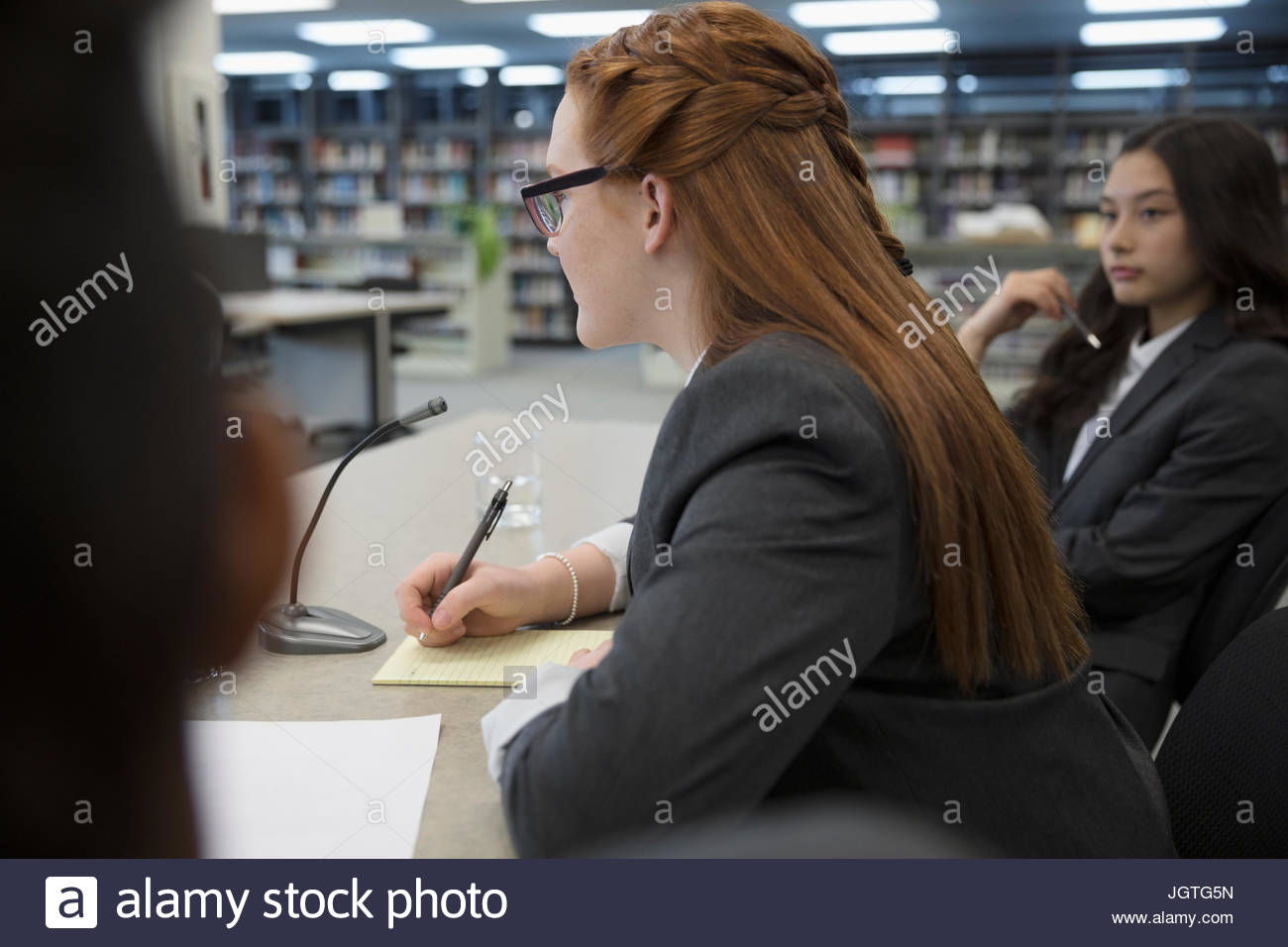 Girl middle school student talking in debate club library - Stock Image