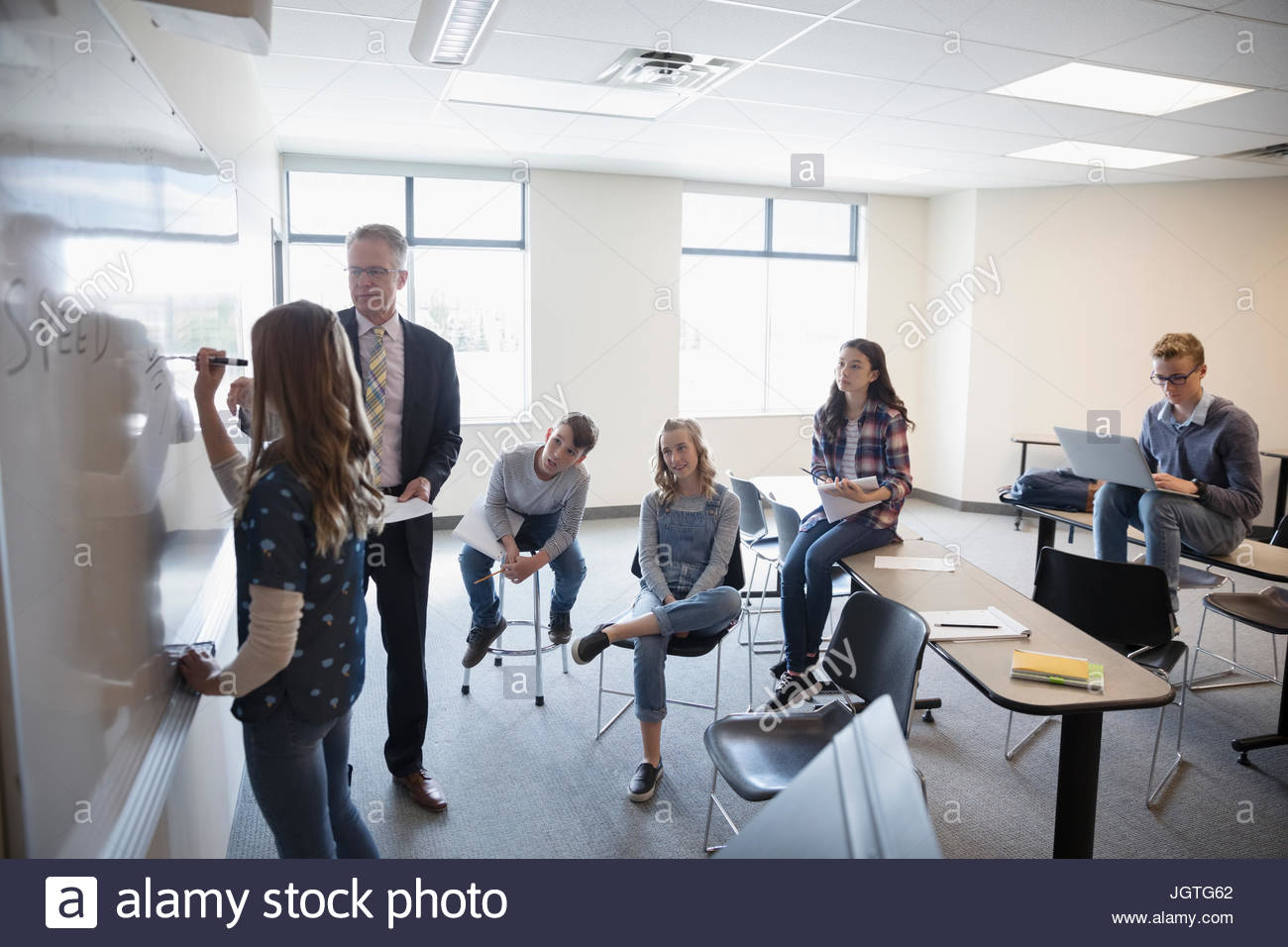 Teacher helping middle school student at whiteboard in classroom Stock Photo