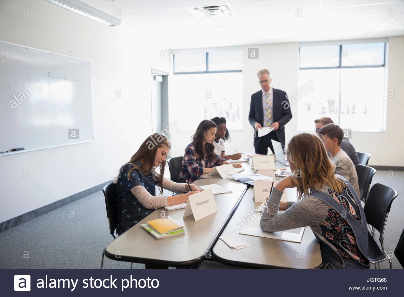 Teacher and middle school students in debate club classroom - Stock Image