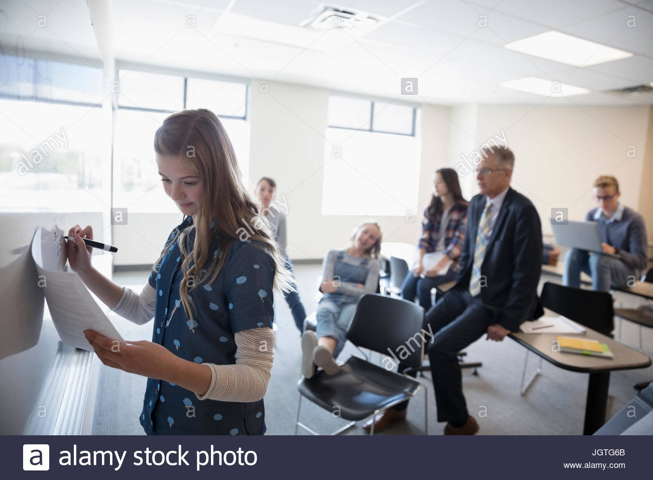 Girl middle school student writing at whiteboard in classroom - Stock Image