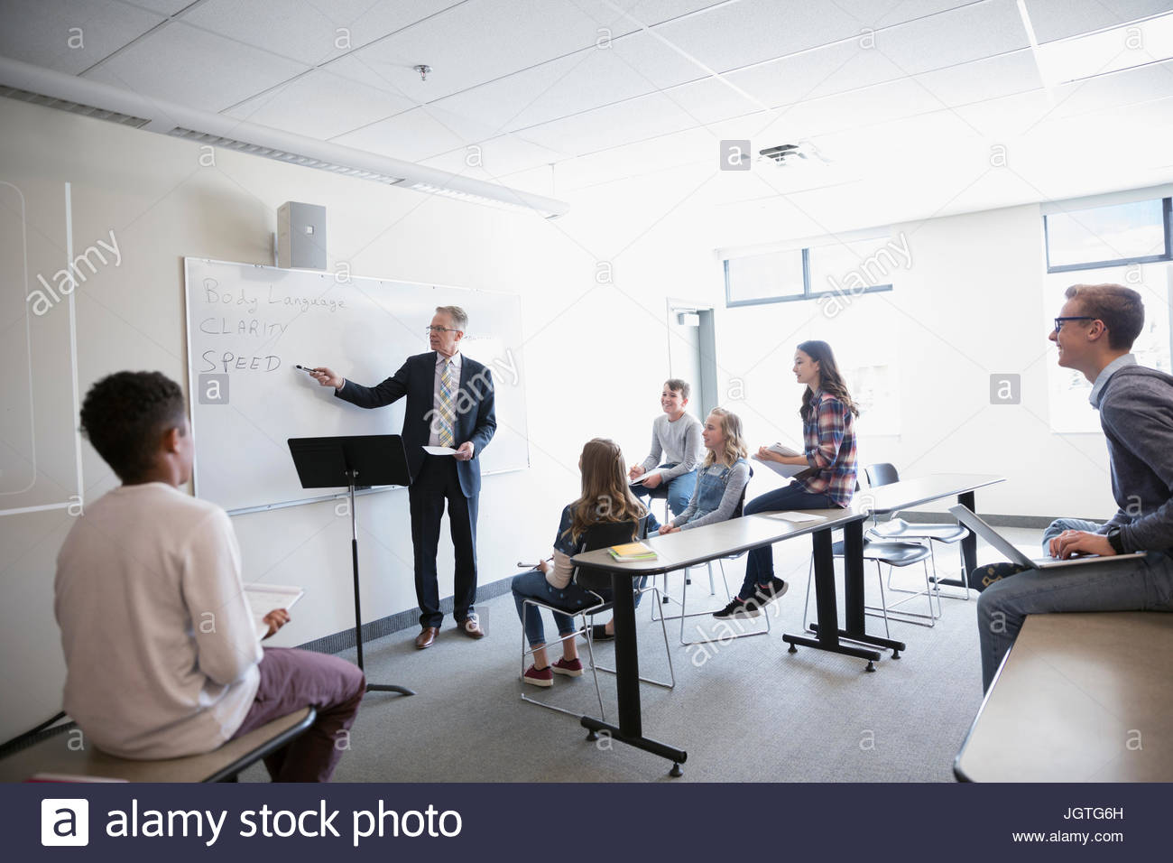 Middle school students listening to teacher leading lesson at whiteboard in classroom - Stock Image